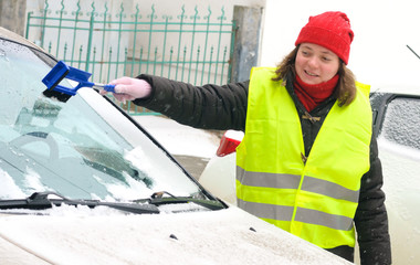 Woman cleans snow car windshield