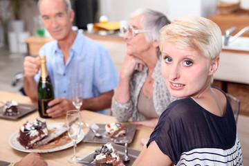 Family gathered around table eating cake