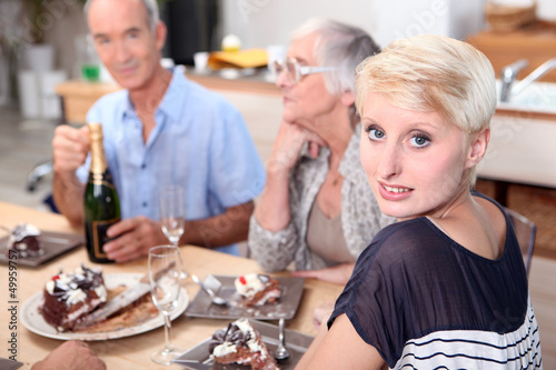 Family gathered around table eating cake