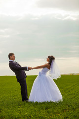 Russia newlyweds couple, bride and groom standing in a field hol