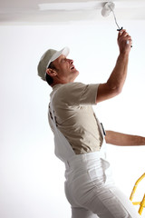 Man repainting ceiling with roller