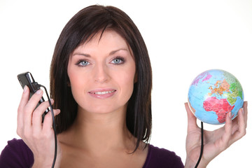 Woman holding globe and telephone
