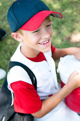Little league baseball player happy after game.