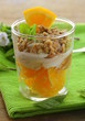 orange dessert with cream and biscuits in a glass
