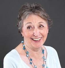Humorvolle ältere Dame lachend mit grauen Haaren