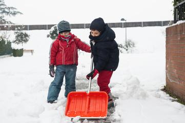 Young kids shoveling snow off sidewalk.