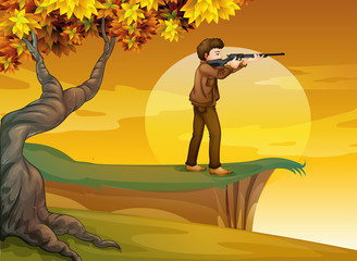 A boy holding a gun near the tree