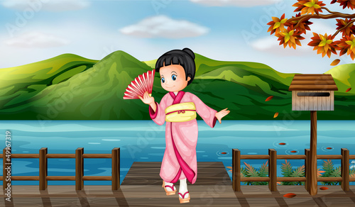 A girl wearing a chinese dress with a wooden mailbox