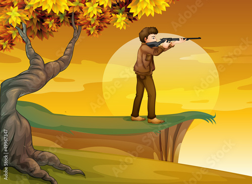 A boy holding a gun near the tree