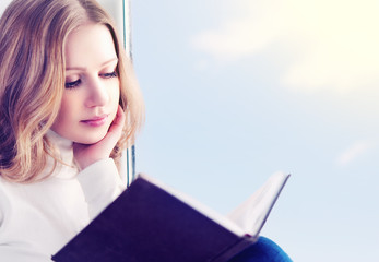 beautiful young woman reading a book while sitting at a window