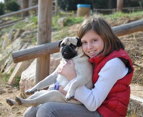 niña con su perro pug
