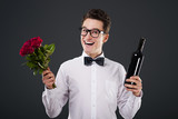 Happy man with a bouquet of roses and wine