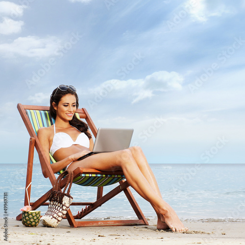 A young and lovely brunette woman relaxing on the beach
