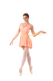 A young and beautiful ballerina in an orange dress