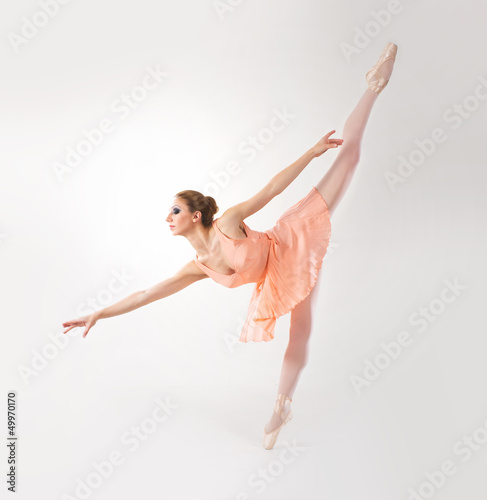 A young and beautiful female ballet dancing on grey