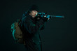 Sniper with beard in black holding gun. Studio shot.