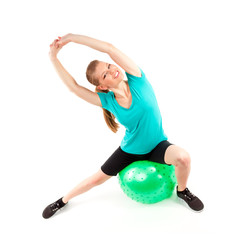 Young cheerful smiling woman exercising with fitball isolated
