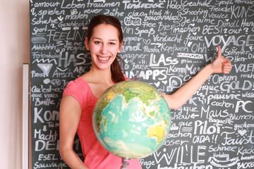 junge Schülerin mit Weltkugel
