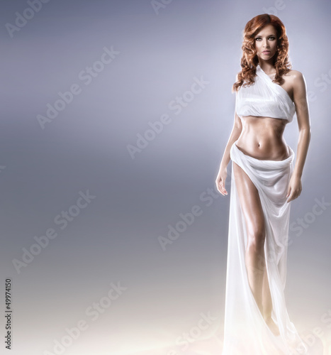A young and sexy redhead woman in a long white dress