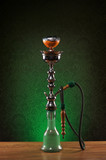 An old ceramic hookah on a dark green vintage background