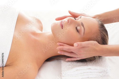 A young blond woman relaxing on a spa massage procedure