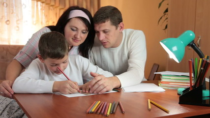 Father and mother helping her son doing homework