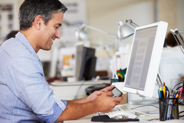 Man Using Mobile Phone At Desk In Busy Creative Office