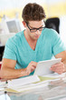 Man Using Digital Tablet In Busy Creative Office
