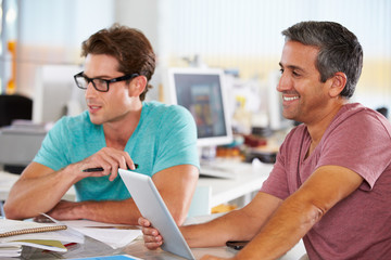 Two Men Using Tablet Computer In Creative Office