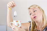 Worker with look of relief holding tea bag and cup