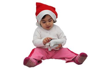 Bambina che osserva il joypad col cappello di Natale