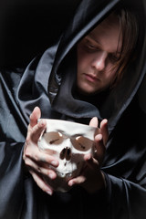 young man with human skull in the hand
