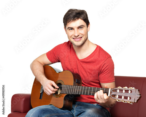 Smiling guitarist plays on the acoustic guitat