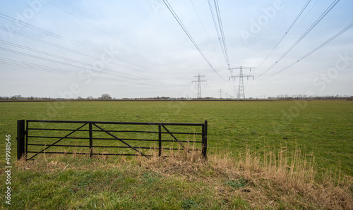 Dutch farmland with a steel fence and high voltage lines.