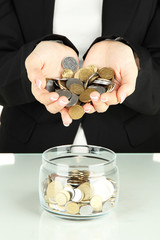 Saving, female hands putting coins into glass bottle, isolated