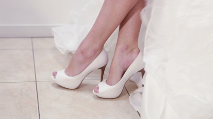 Bride is trying on her wedding dress and shoes