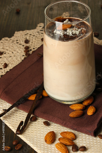 Glass of chocolate-cream cocktail on wooden table close-up