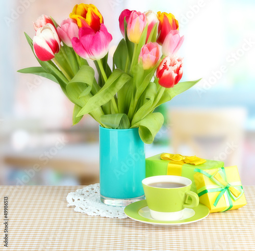 Beautiful tulips in bucket with gifts and cup of tea