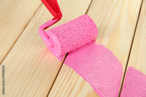 Paint roller brush with pink paint, on wooden background