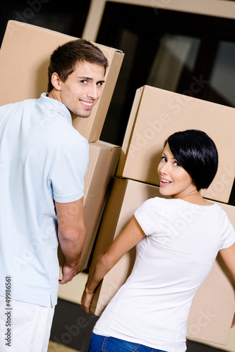 Back view of happy couple carrying cardboard packages