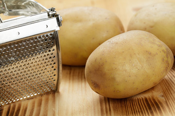 Kartoffelpresse und Kartoffeln
