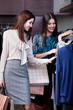 Friends are seeking for a dress at the ready-made clothes shop