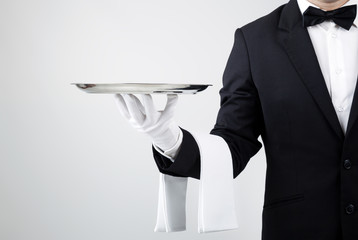 Waiter holding empty silver tray over gray background