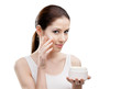 Woman applying lifting cream from container on face