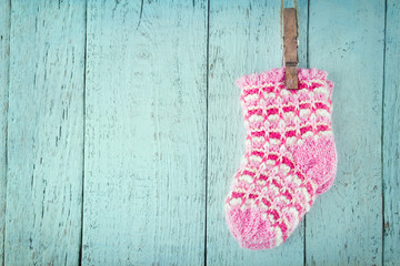 Pink baby socks on a blue wooden background
