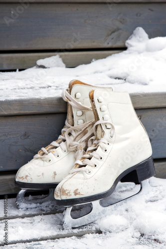 Pair of old white skates on snowy stairs