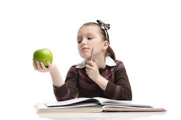 Little girl hesitates about eating a ripe green apple
