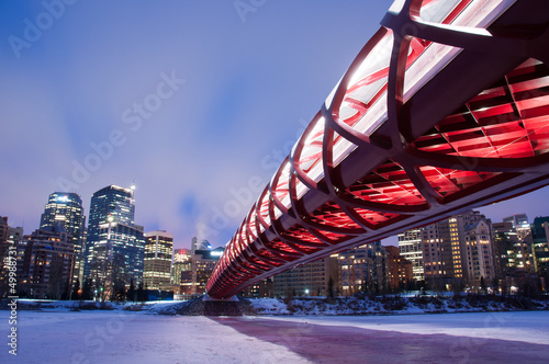 Calgary skyline and pedestrian bridge at night.