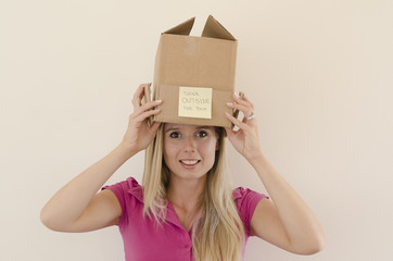 girl removing the box from her head
