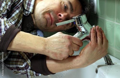 Mann installiert Wasserhahn an Waschbecken
